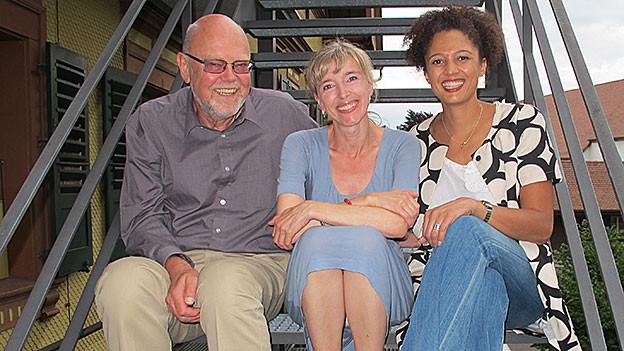 Christian Schmid, Anita Richner und Sivliva Binggeli posieren sitzend auf einer Treppe.