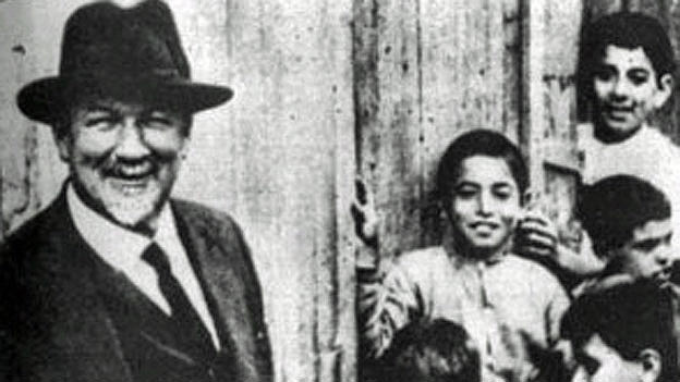 Jakob Künzler lacht in die Kamera - neben ihm Kinder. Schwarzweiss Aufnahme.