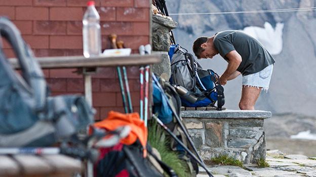 Ein Wanderer packt bei einer Hütte seinen Rucksack.