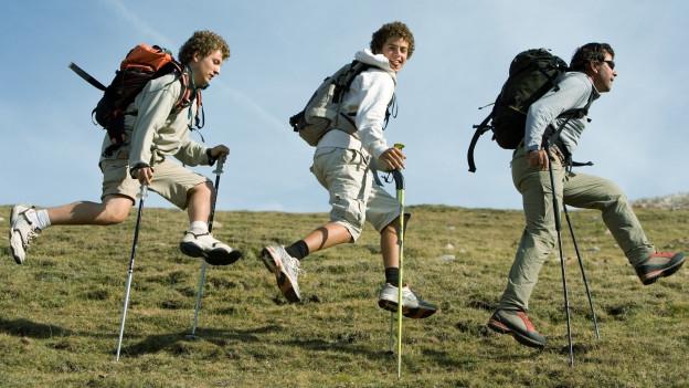 Menschen, die mit Wanderstöcken wandern.