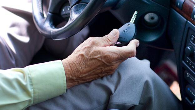 Eine ältere Person sitzt im Auto und hält den Autoschlüssel in der Hand.