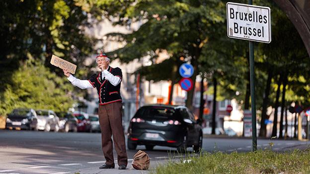 Mann in Schweizer Sennentracht macht in Brüssel Autostopp.