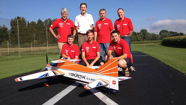 Schweizer Modellkunstflieger-Team posiert mit einem Flugzeug.