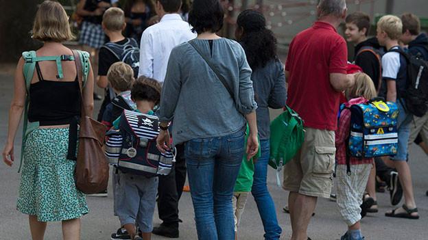 Eltern begleiten Kinder in die Schule.