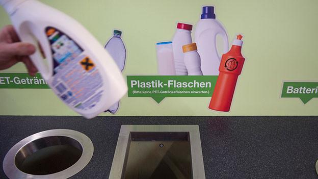 Jemand wirft Plastikflasche in den Container bei der Entsorgungsstelle im Grossverteiler.