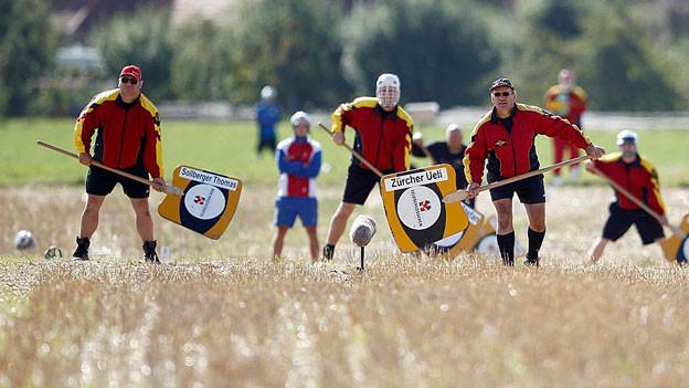 Hornusser stehen auf einem Feld bereit.