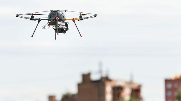 Eine Drohne fliegt über einen Acker neben einem Wohngebiet.