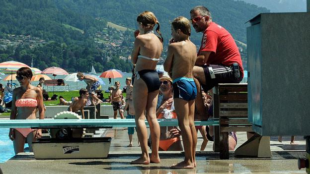 Ein Bademeister sitzt am Beckenrand, um ihn herum stehen Kinder.