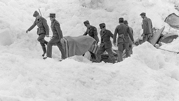 Soldaten und Polizisten tragen zugedeckte Leichen über ein Schneebrett.