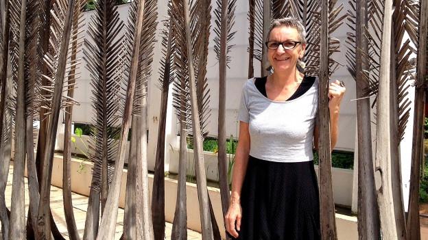 Sonja Weder steht vor einem Arrangement aus grossen Zweigen der Kokospalme, die aufgestellt sind und eine Art Wand bilden