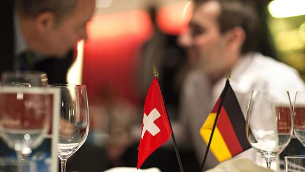 Tischfähnchen Schweiz und Deutschland – im Hintergrund sprechen zwei Männer miteinander.