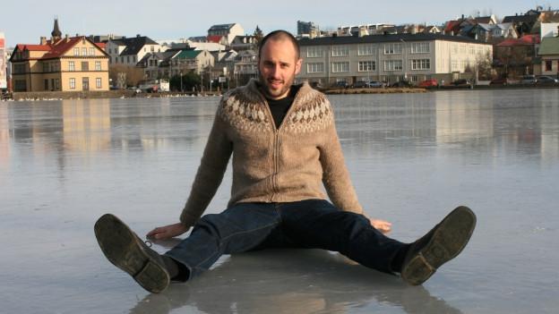 Der junge Auslandschweizer Joachim Schmidt sitzt auf einem eisgefrorenen See in der isländischen Stadt Reykjavik