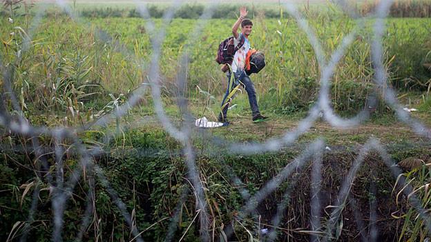 Ein junger Mann geht auf einem Weg, im Vordergrund der Grenzzaun.