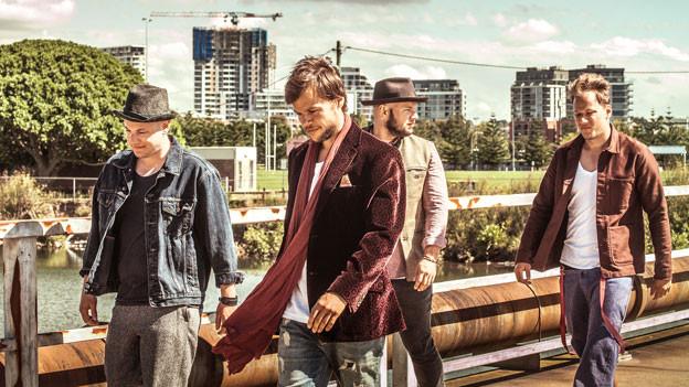 Die vier Brüder gehen über eine Brücke, im Hintergrund sind Wohnblocks zu sehen.