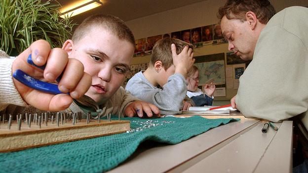 Ein behinderter Junge sitzt am Pult und arbeitet mit Nägeln und Zange auf einem Brett.