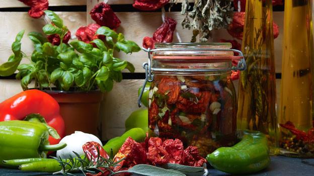 Frisches und gedörrtes liegt neben eingelegtem Gemüse in einem Glas.