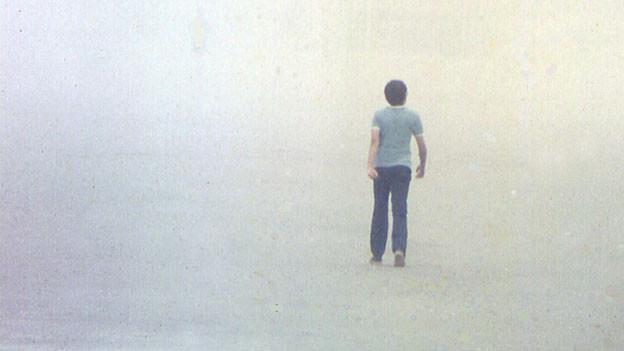 Ein Knabe spaziert im Nebel, von hinten fotografiert.