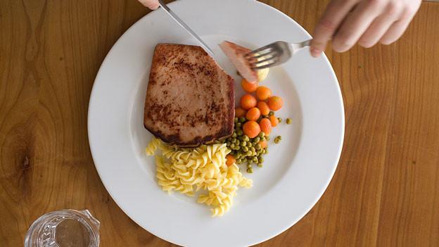 Fleischkäse, Erbsen, Karotten und Nudeln auf einem weissen Teller.