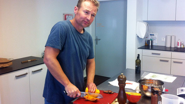 Daniel Tinembart schneidet in der Küche einen Kürbis.