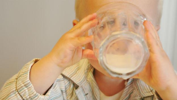 Kind trinkt Milch aus dem Glas.
