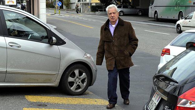 Ein älterer Mann ist auf einem Fussgängerstreifen unterwegs, daneben stehen zwei Autos.