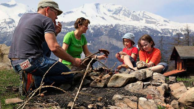 Ein Mann, eine Frau und zwei Kinder grillieren bei einer Feuerstelle in den Bergen.