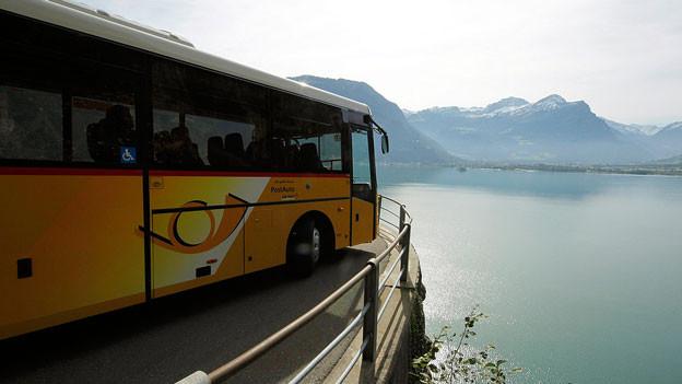 Ein Postauto ist unterwegs auf einer Strasse über dem See.