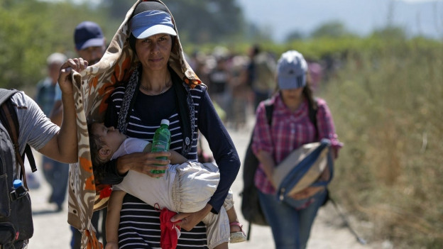 Flüchtlingsfrau läuft mit schlafendem Kind auf den Armen einen Weg entlang.