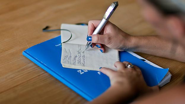 Hand hält Stift über Notizblock.