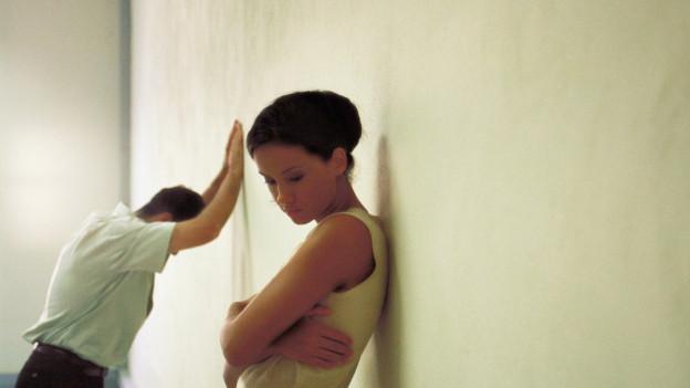 Zwei Menschen, an eine Wand gelehnt, voneinander abgewandt