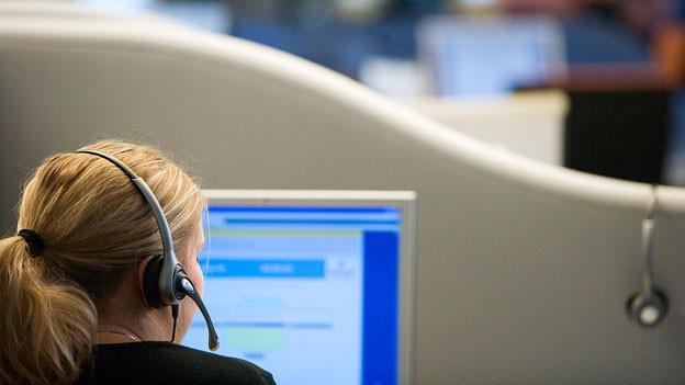 Eine Frau im Callcenter telefoniert mit einem Headset.