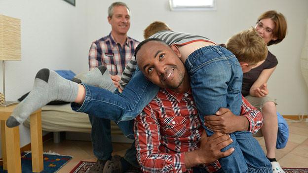 Ein eritreischer Mann spielt mit zwei Schweizer Kindern im Wohnzimmer, im Hintergrund die beiden Eltern der Kinder.