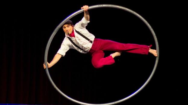 Akrobat Pascal Häring dreht in einem grossen Metallring auf der Bühne.