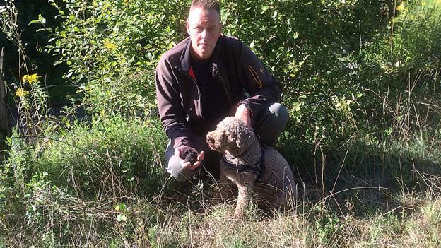 Ein Mann posiert mit seinem Trüffelhund in einer Wiese.