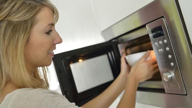 Frau stellt Essen in den Mikrowellenherd.