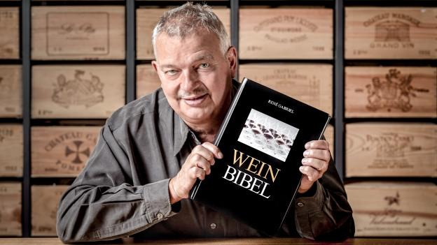 Autor René Gabriel hält die Weinbibel in die Kamera.