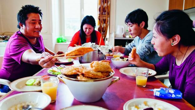 Tibetische Flüchtlingsfamilie sitzt am Tisch und isst.
