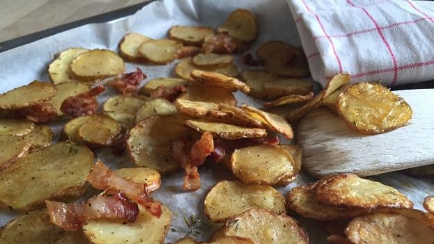 Kartoffelscheiben auf einem Blech mit knusprigem Speck und Käse überbacken