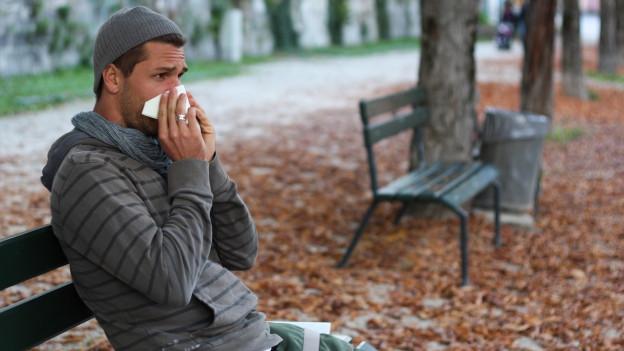 Mann sitzt auf Parkbank und schnäuzt in ein Taschentuch.