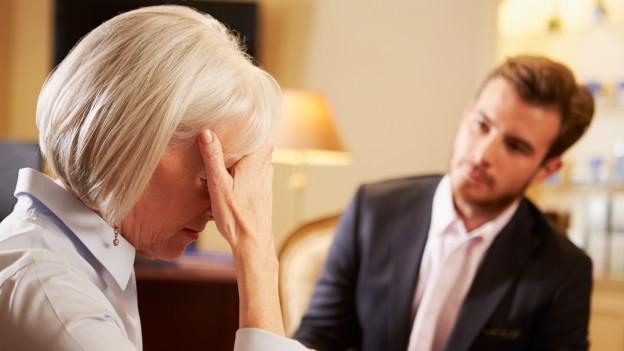 Frau spricht im Büro mit ihrem Chef.