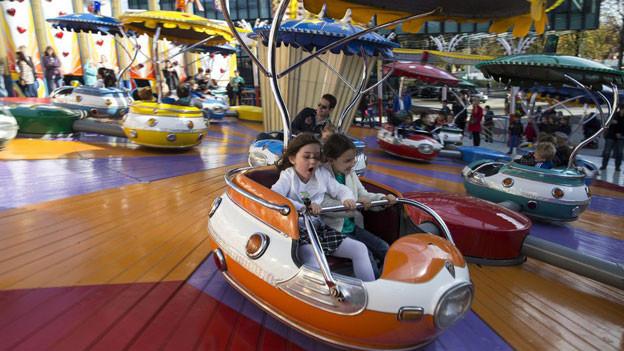 Zwei Kinder sitzen in der Calypso - Bahn in voller Fahrt.