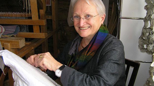 Barbara Wälchli stickt auf weissen Stoff.