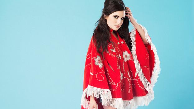 Whitney Rose in rot-weissem Kleid vor türkisfarbenem Hintergrund.