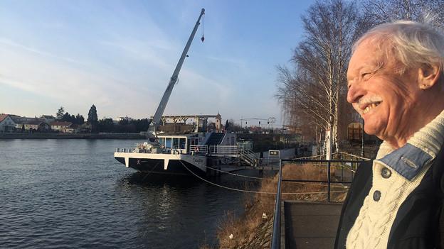 Rene Bolliger steht am Ufer und blickt aufs Wasser und ein Schiff.