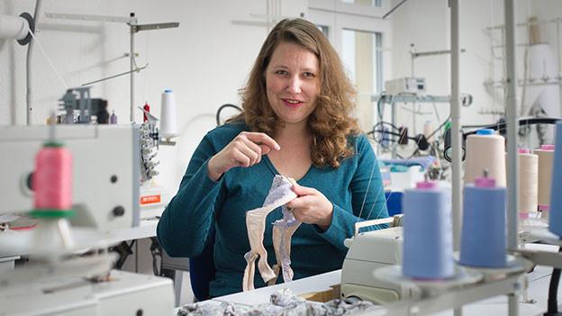 Christine Meixner hält in ihrem Atelier einen BH in der Hand.