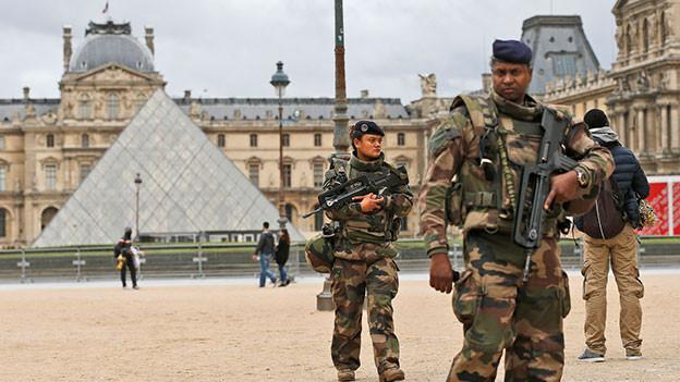 Bewaffnete Militärs patroullieren vor dem Louvre.