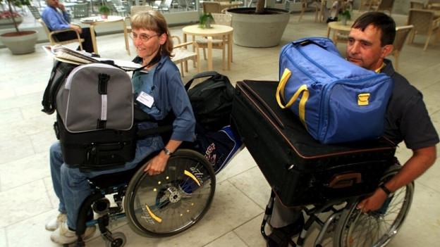 Zwei Rollstuhlfahrer sind mit viel Gepäck auf den Knien unterwegs.