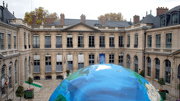 Gebäude mit Innenhof und grosser Weltkugel im Vordergrund.