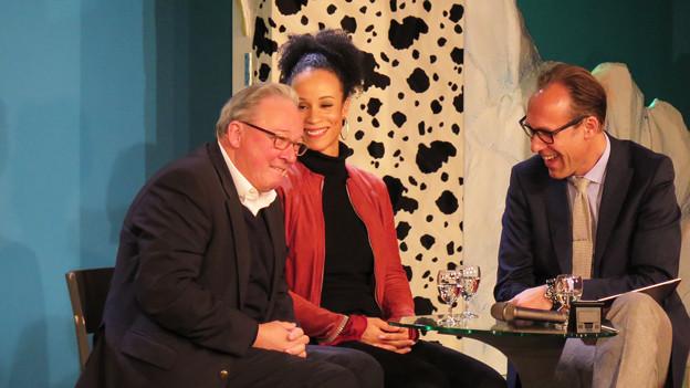 Die drei Gesprächsgäste sitzen auf der Bühne und reden.