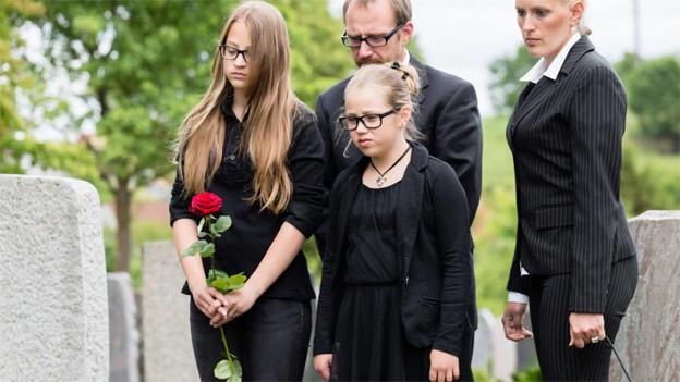 Trauerfamilie steht am Grab.